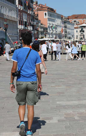 Young tourist walks in Venice Italy in summer and many people