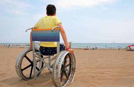 disabled boy on a wheelchair on the beach admires the sea
