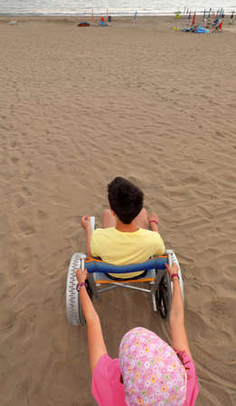 little girl pushes the wheelchair on the sandy beach with a young boy in summer Imagens