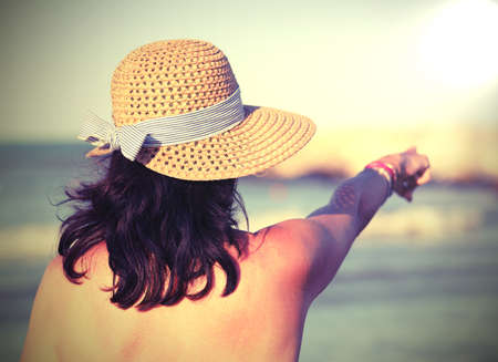 nice girl with straw hat and long hair by the sea in summer