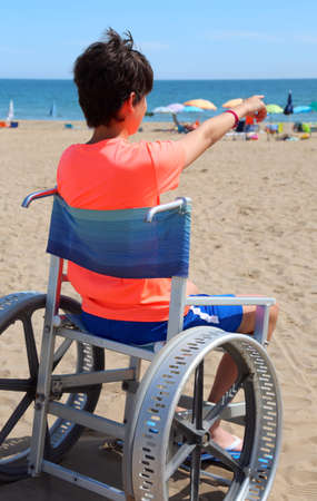 Child on the special wheelchair to go on the sandy beach in summer