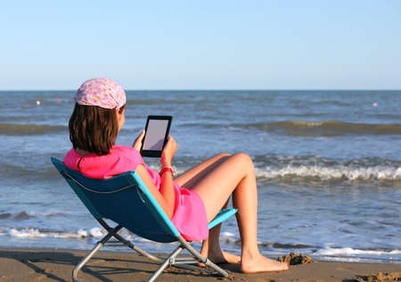 little girl reads the ebook in summer by the sea
