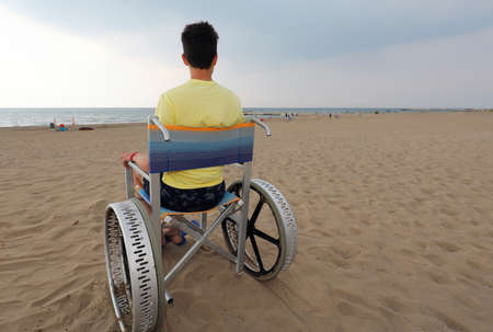 young boy with yellow t-shirt on special wheelchair on the sandy beach in summer Imagens