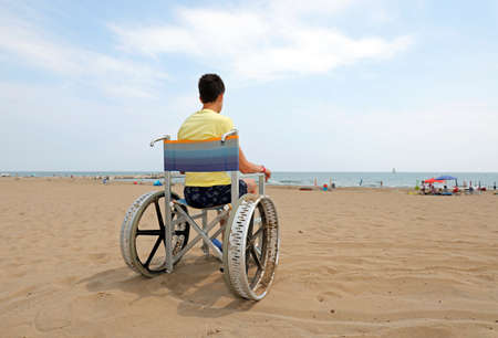 disabled boy sitting on a wheelchair on the beach facing the sea
