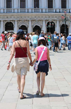 young mother and her daughter walking on the Saint Mark Square in Venice in Italy in Summer and more people Stock fotó