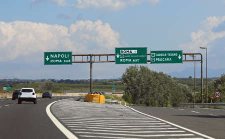 italian road signs on motorway near Rome City and the arrows directions to Naples and more cars