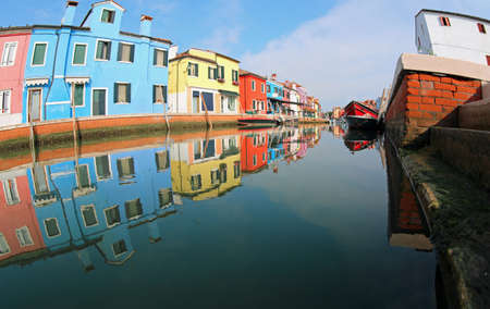 Colored House of Burano Island near Venice in summer and the navigable canal without people Banco de Imagens