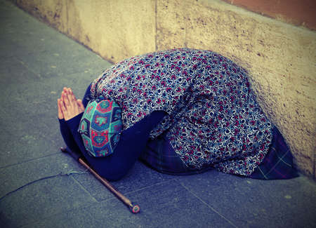 old gypsy asked for alms on the edge of the sidewalk of a metropolis