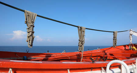 big red lifeboat with ropes in a cruise ship off the ocean