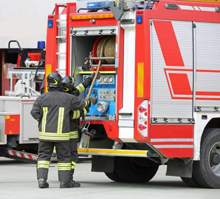 fire engine and two firemen in action during the fire Banque d'images - 130217606