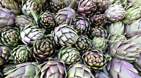 background of many green artichokes for sale at the vegetable market
