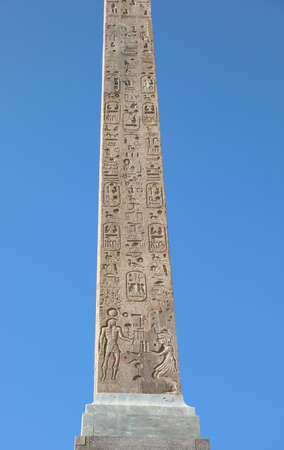 Old Egyptian Obelisk with hieroglyphs and blue sky on background
