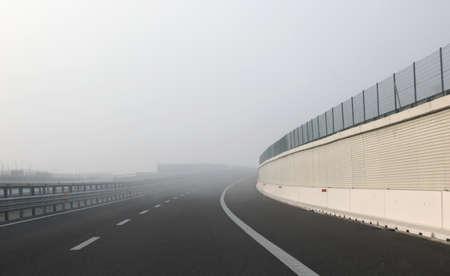 Dangerous curve of the desert highway with dense fog in winter