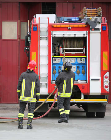 two firefighters and the fire turck during an emergency on the city Banque d'images - 130349101
