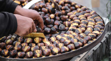 street vendor with a stall selling roasted chestnuts