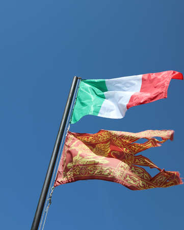 Italian flag and Venetian Flag on the blue sky