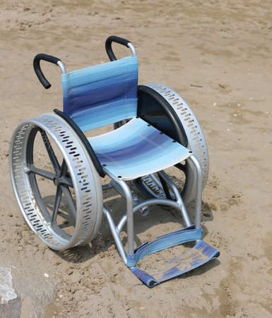 wheelchair with large aluminum wheels on the sand of the beach without any person