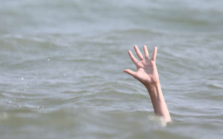 drowning bather holds up his hand for help Stock Photo