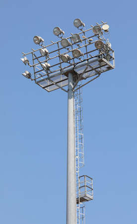 many floodlights in the pole at stadium without people and blue sky on background