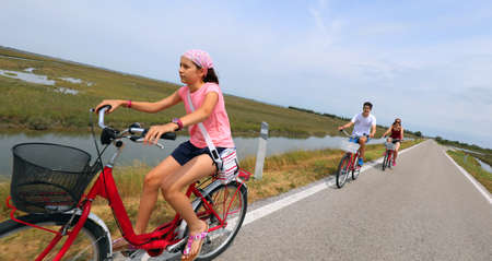 Pretty little girl with bandana on the bike in summer and his family on the road with slanted horizont intentionally