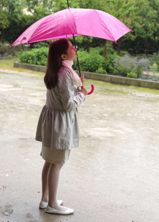 elegant little girl is in the thick rain with a pink umbrella
