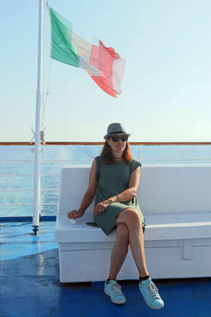 Pretty woman with hat on the cruise liner with italian flag