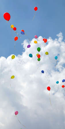 Many colorful balloons fly into the blue sky with many white clouds i Reklamní fotografie