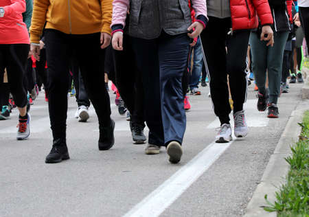 many people walk down the street during a winter demonstration in the city