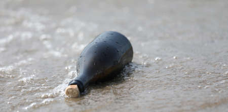 glass bottle with a message carried on the shore by the waves