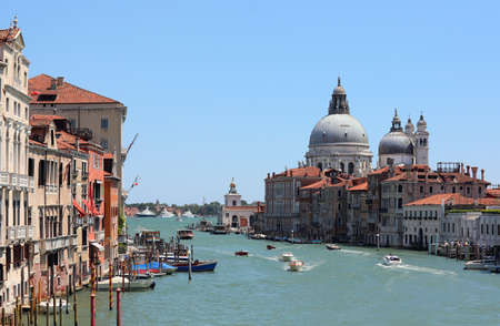 typical view of the island of Venice in Italy with the Grand Canal which is the main communication route of the city and the great Dome of the Church called Madonna della Salute photographed from the Accademia Bridge and many boats Banco de Imagens