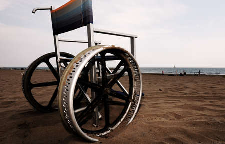 wheelchair with big wheel on the sandy beach with dark toned effect Reklamní fotografie