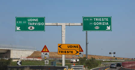 motorway junction with road signs with the arrows with the detour for the Italian cities of Palmanova and Udine and to go to the border with Croatia and Austria Reklamní fotografie