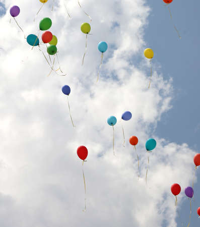 Many colored balloons fly into the blue sky with white clouds in summer during the party