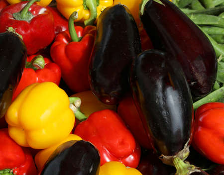 ripe aubergines also called Eggplants and yellow and red peppers for sale at greengrocer stand at local market Фото со стока