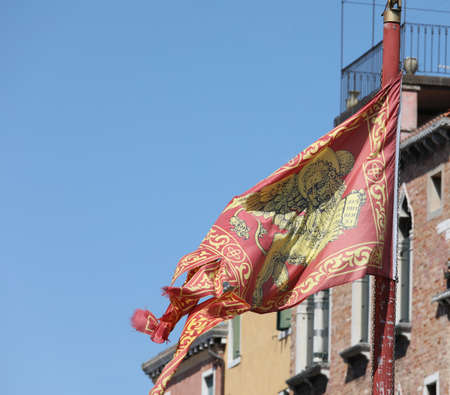 Venetian flag with winged lion waving on the wind in Venice Italy
