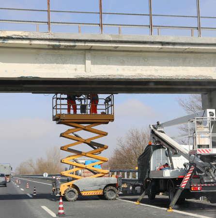 men at work to maintenance a bridge over highway