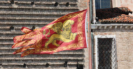 Golden Winged Lion on the Red Flag is the symbol of Serenissima in Venice in Italy Фото со стока