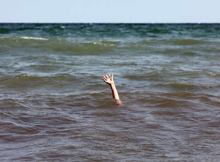 hand of the person asking for help while drowning in the sea