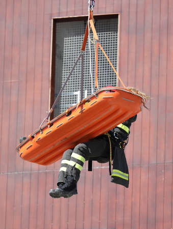 special stretcher for the rescue of the injured is lowered with the rope from a high skyscraper during the fire