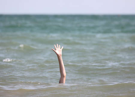 hand of the person during the drowning in the sea asking for help