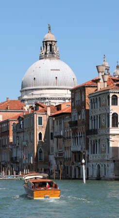 Taxi boat and the Dome of the Church called Madonna della Salute in Venice Italy 写真素材