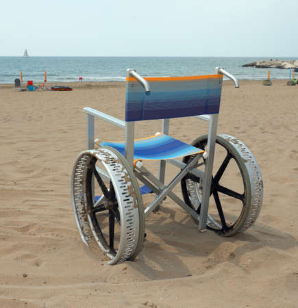 wheelchair with big wheels made with alloy of aluminium to move on the sandy beach on summer without people