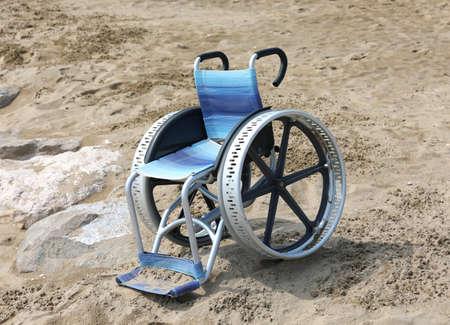 locked wheelchair with large aluminum wheels on th sandy beach in summer Stok Fotoğraf