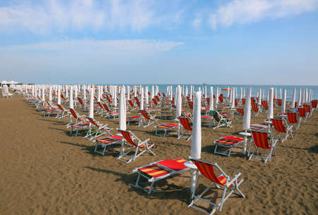 sun umbrellas with deckchairs on the beach without people in the early morning and the sea in the background