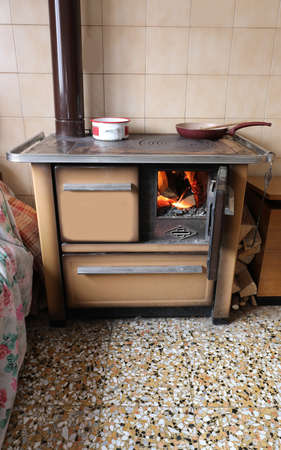very old wood stove with a blazing fire and the pots with hot items
