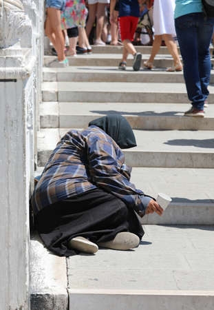 old woman squatting on the street begging people Imagens