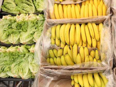 yellow bananas and green lettuce for sale at local market
