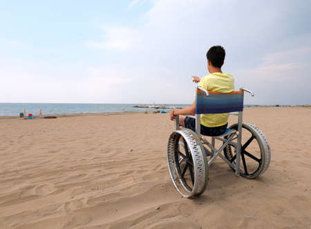 young boy with yellow vest on the wheelchair at beach Stock Photo