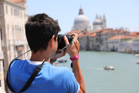young photographer with camera while taking pictures of the island of Venice in Italy from the Accademia bridge