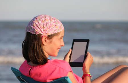 Pretty little girl reads her ebook in summer 版權商用圖片